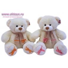 Медведь в шарфе и с бантами на шарфе и на пятках - музыкальная игрушка