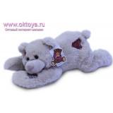 Бежевый медведь Семен лежит на животе